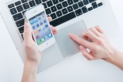 White iphone 4 4s. In women's hands next to macbook pro Stock Photography