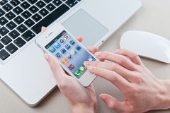 White iphone 4 in women's hands. White iphone 4 4s in women's hands next to macbook pro Stock Photo