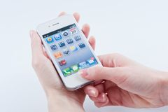White iphone 4S. Women's fingers with a manicure keeps White iphone 4 on a white Stock Photography