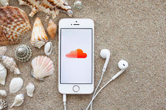 White iPhone 5s with app Sound Cloud on the screen lying on the Royalty Free Stock Photo