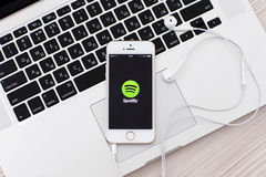 White iPhone 5s with site Spotify on the screen and headphones l Royalty Free Stock Photo