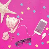 White iPhone, starfish, seashells of different sizes are on an ultraviolet background. stock photos
