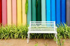 White iron bench and multicolor concrete fence. In the garden royalty free stock images
