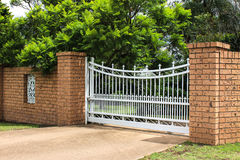 White iron driveway entrance gates in brick fence. White wrought iron entrance gates set in brickwork Stock Photo