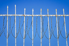 White iron fence with a barbed wire against the blue sky Stock Images