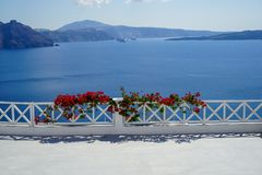 White island balcony with dark pink red Bougainvillea flower foreground in front of scenic mediterranean sea view and caldera. Mountain background, Santorini stock photo