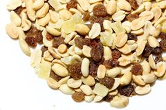 On a white isolated background lies a mixture of nuts and fruits. The mixture consists of peanuts, candied fruits, raisins and dried bananas stock photography