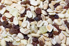 On a white isolated background lies a mixture of nuts and fruits. The mixture consists of peanuts, candied fruits, raisins and dried bananas stock images