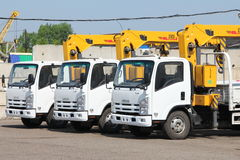 White Isuzu flatbed trucks with yellow crane arm is in parking lot - Russia, Moscow, 30 August 2016 Royalty Free Stock Images