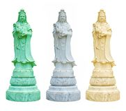 White, ivory and green statues of Guanyin hold a vase of holy water royalty free stock photo