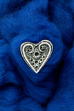 White ivory heart shape on blue woolen textile Stock Image