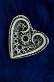 White ivory heart shape on blue woolen textile Royalty Free Stock Images