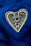 White ivory heart shape on blue woolen textile Stock Photography