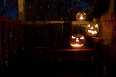 White jack o'lanterns on a bench at night Stock Photos