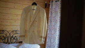 White jacket hanging from a chandelier in a wooden house stock video