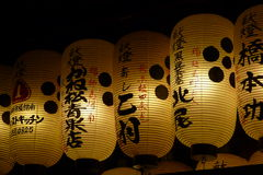 White Japanese lanterns with Kanji at night. Night photo of a row of lighted white Japanese lanterns with Kanji written Stock Photo