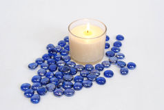 White candle with blue beads. White jar candle with blue glass beads Royalty Free Stock Images
