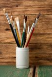 White jar with paintbrushes on green board Stock Photo