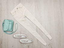White jeans and sneakers, mint bag. Fashionable concept. Wooden background Royalty Free Stock Images