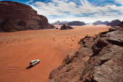 White jeep between the mountains. Anonymous car in the sand of Wadi Rum reservation, Jordan royalty free stock image