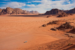 White jeep in a Wadi Rum desert,. Small jeep in a huge desert of Wadi Rum. Shot from the only massive sand dune stock image