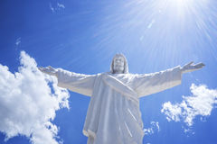 White Jesus Cusco Peru. White Jesus with outstretched arms and lens flare above him. Statue stands  on top of a mountain of the city Cusco, Peru Royalty Free Stock Image