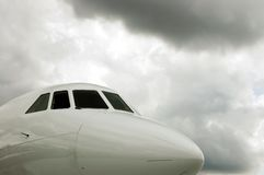 White Jet Cockpit and storm clouds. The nose of a white jet plane under stormy skies Stock Photos