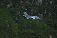 White Jet Fighter Aircraft on Top of Green Mountain Royalty Free Stock Images