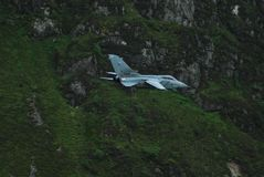 White Jet Fighter Aircraft on Top of Green Mountain Stock Image