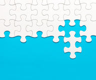 White jigsaw puzzle on blue background Royalty Free Stock Image