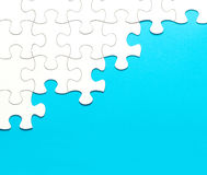 White jigsaw puzzle on blue background Stock Images