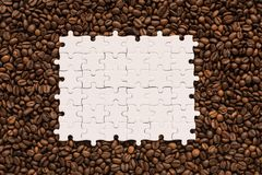 White jigsaw puzzle on coffee beans background. Copy Space royalty free stock image
