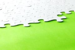 White jigsaw puzzle on green background Stock Image