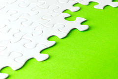 White jigsaw puzzle on green background Royalty Free Stock Image