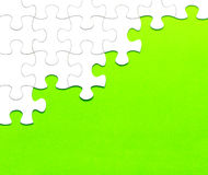 White jigsaw puzzle on green background Stock Photos