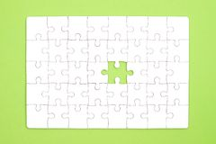 White jigsaw puzzle on green background.  Stock Images