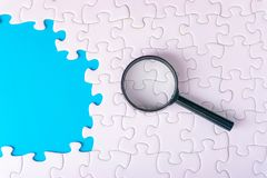 White jigsaw puzzle, Magnifier and missing pieces with selective focus and crop fragment. Business and education concept stock image