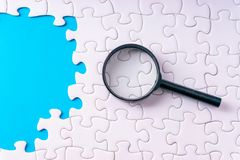 White jigsaw puzzle, Magnifier and missing pieces with selective focus and crop fragment. Business and education concept royalty free stock images