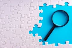 White jigsaw puzzle, Magnifier and missing pieces with selective focus and crop fragment. Business and education concept royalty free stock photo