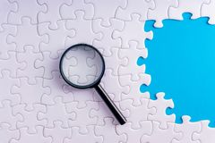 White jigsaw puzzle, Magnifier and missing pieces with selective focus and crop fragment. Business and education concept stock images
