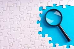 White jigsaw puzzle, Magnifier and missing pieces with selective focus and crop fragment. Business and education concept royalty free stock photography