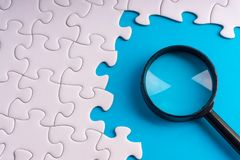 White jigsaw puzzle, Magnifier and missing pieces with selective focus and crop fragment. Business and education concept royalty free stock photos