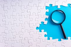 White jigsaw puzzle, Magnifier and missing pieces with selective focus and crop fragment. Business and education concept stock photography