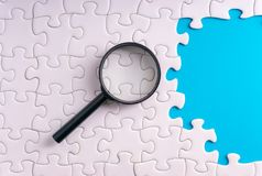White jigsaw puzzle, Magnifier and missing pieces with selective focus and crop fragment. Business and education concept stock photo