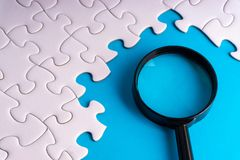 White jigsaw puzzle, Magnifier and missing pieces with selective focus and crop fragment. Business and education concept royalty free stock image