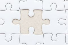 White jigsaw puzzle with missed piece. Close up of White jigsaw puzzle with missed piece royalty free stock image