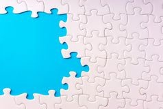 White jigsaw puzzle and missing pieces with selective focus and crop fragment. Business and education concept stock image