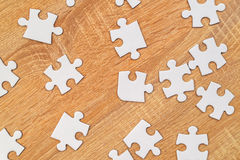 White jigsaw puzzle pieces scattered on wooden table. Blank white jigsaw puzzle pieces scattered on wooden table, top view Royalty Free Stock Photo
