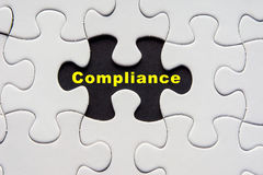 White jigsaw puzzle with a written word Compliance Royalty Free Stock Image
