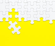 White jigsaw puzzle on yellow background Stock Photo